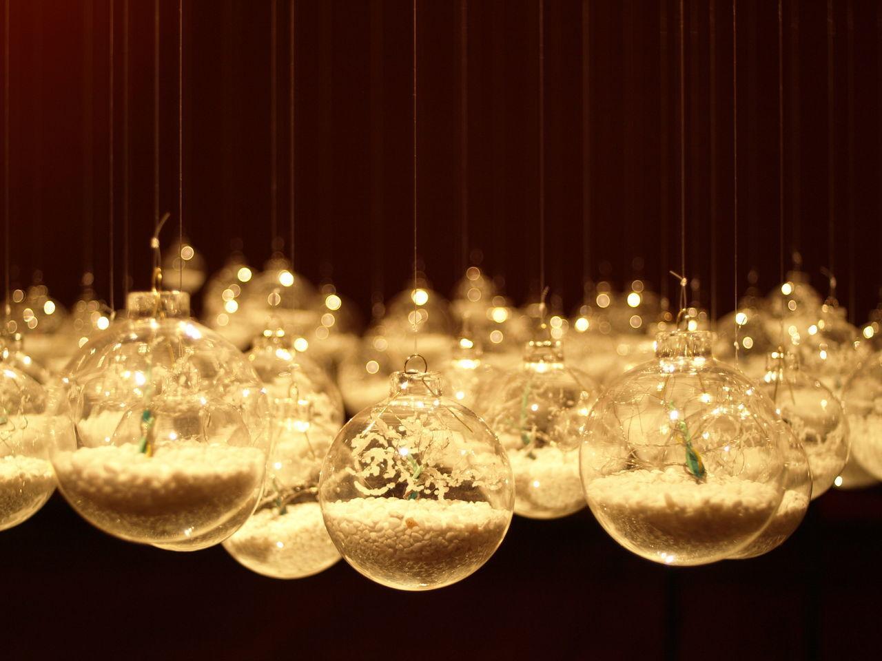 CLOSE-UP OF ILLUMINATED LANTERNS HANGING IN GLASS