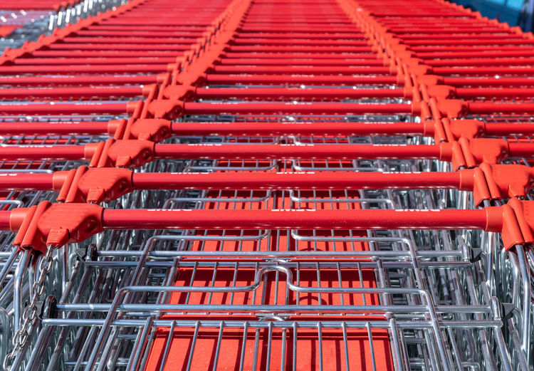 In A Row Red Trolley Abundance Close-up Consumerism Convenience Day Food And Drink Full Frame High Angle View In A Row Large Group Of Objects Metal No People Order Outdoors Red Retail  Shopping Shopping Cart Steel Store Supermarket End Plastic Pollution