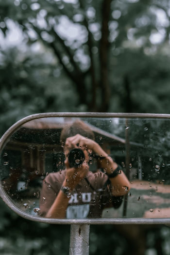 Reflection of woman photographing on wet windshield during rainy season