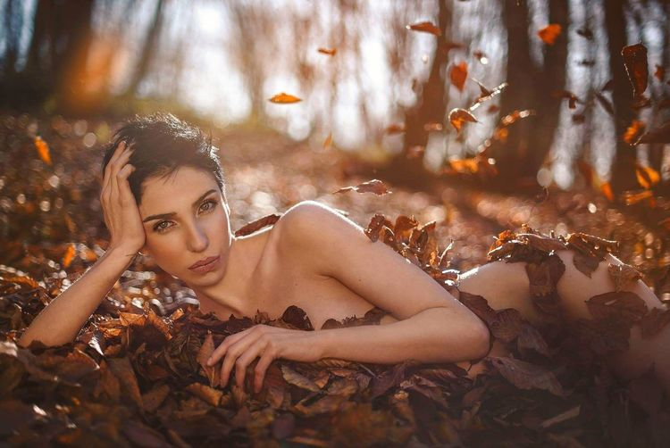 Portrait of naked young woman lying down amidst leaves on field