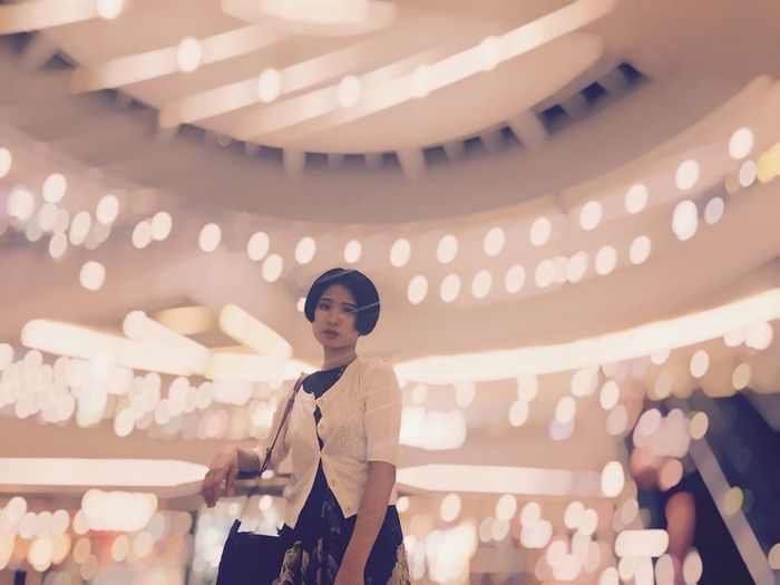 Low Angle Portrait Of Young Woman Against Illuminated Christmas Lights At Shopping Mall