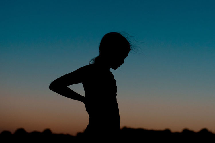 Silhouette woman standing against clear sky during sunset
