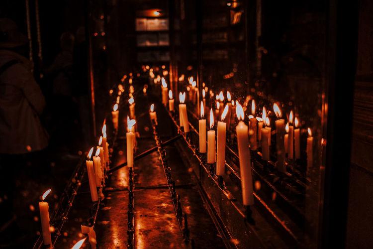 Illuminated candles at altar