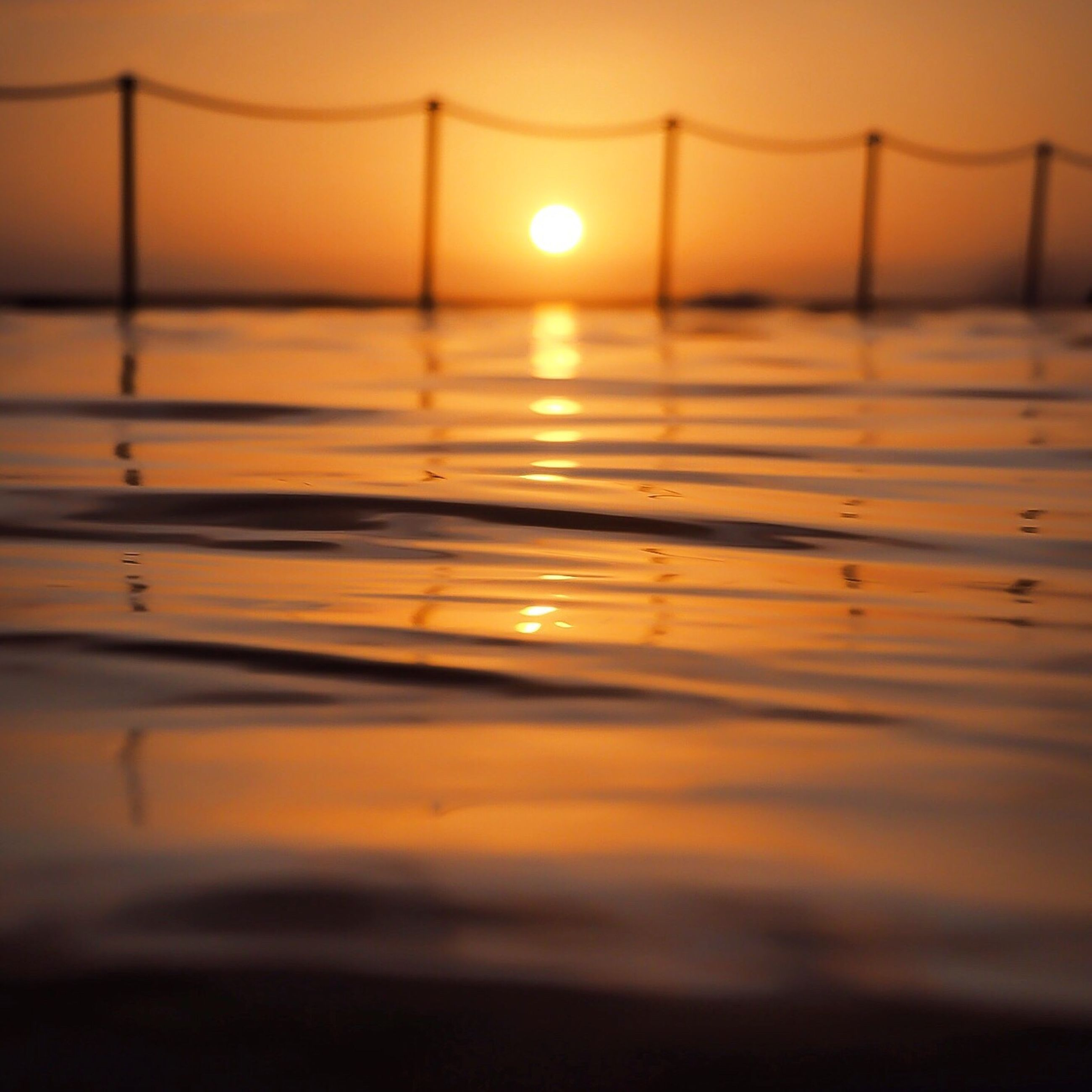sun, sunset, scenics, selective focus, tranquil scene, tranquility, idyllic, orange color, beauty in nature, surface level, sea, sky, majestic, nature, water, outdoors, shore, atmospheric mood, vibrant color, seascape, dramatic sky, water surface