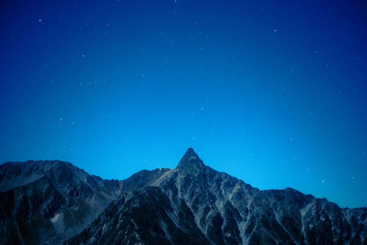 Scenic view of mountains against clear blue sky at night