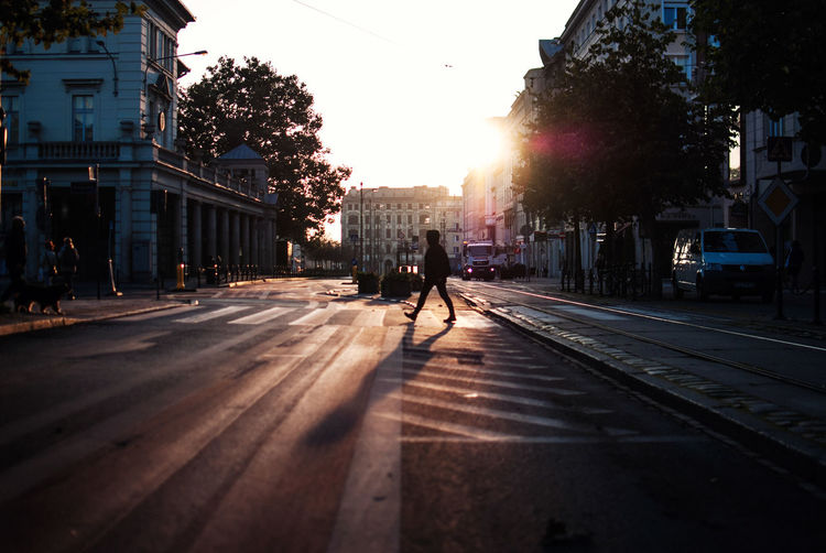 Man Walking On Road In City During Sunset