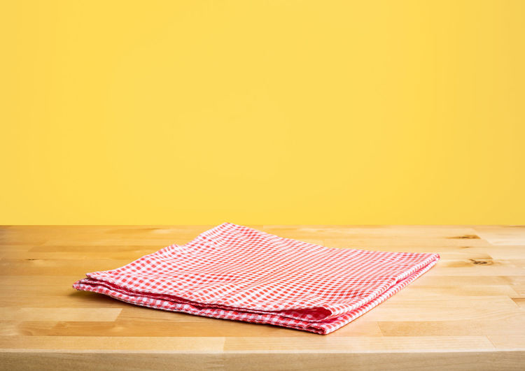 High angle view of umbrella on wooden table against yellow background