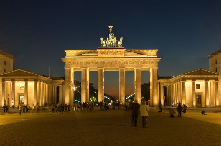 Brandenburger Gate in Berlin, Germany against clear sky Berlin Berlin Mitte Brandenburg Gate Sightseeing Architectural Column Architecture Brandenburger Tor Building Exterior Built Structure City City Gate Germany History Illuminated Large Group Of People Low Angle View Memorial Men Monument Night Outdoors Pariser Platz People Real People Sculpture Sky Statue Tourism Travel Travel Destination Travel Destinations Triumphal Arch Urban Icon Vacations
