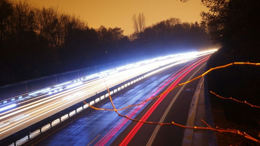 High Angle View Of Light Trails Over Road Amidst Silhouette Trees