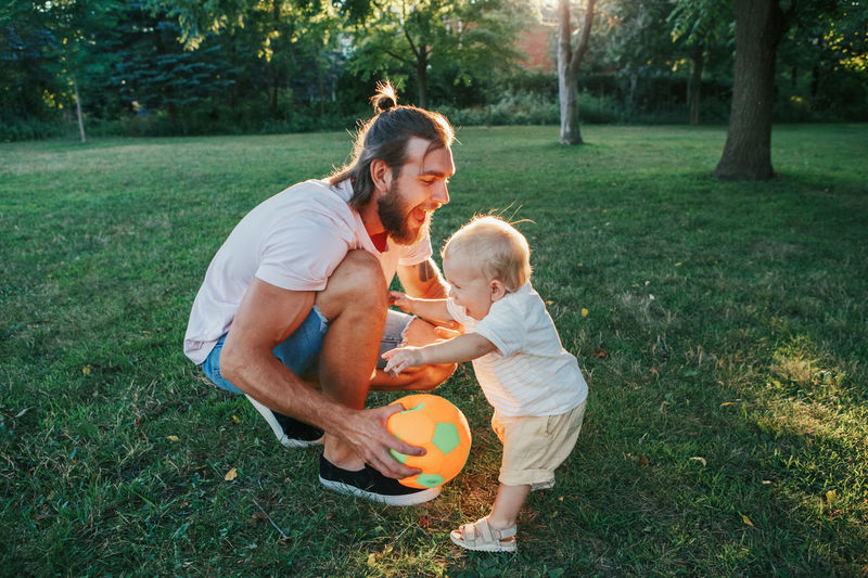 Fathers day. father playing ball with toddler baby boy outdoor. happy dad and active family life.