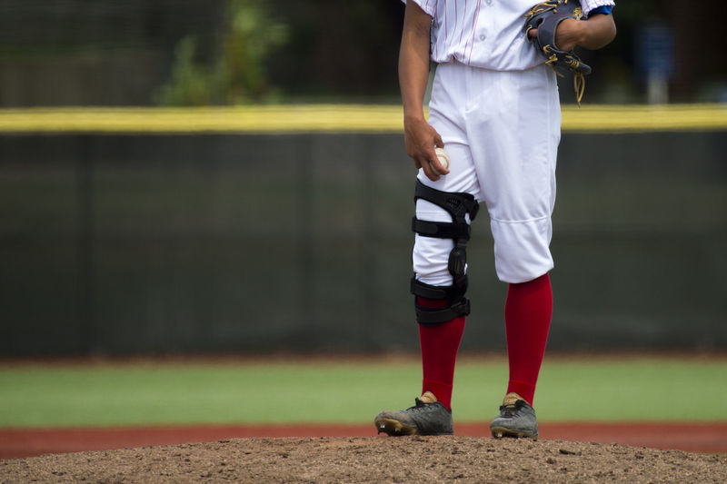 close up of baseball players legs with red stockings standing on first base_a Baseball Athlete Clothing Day Focus On Foreground Front View Holding Human Body Part Leisure Activity Lifestyles Low Section Men One Person Outdoors Playing Playing Field Real People Sport Sports Clothing Standing Teenager Uniform