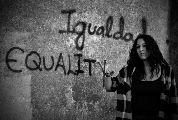 Portrait of young woman gesturing against graffiti wall