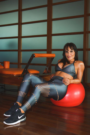 Portrait of smiling woman sitting on fitness ball at gym