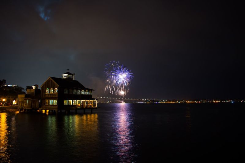 Firework display over river by illuminated buildings in city at night