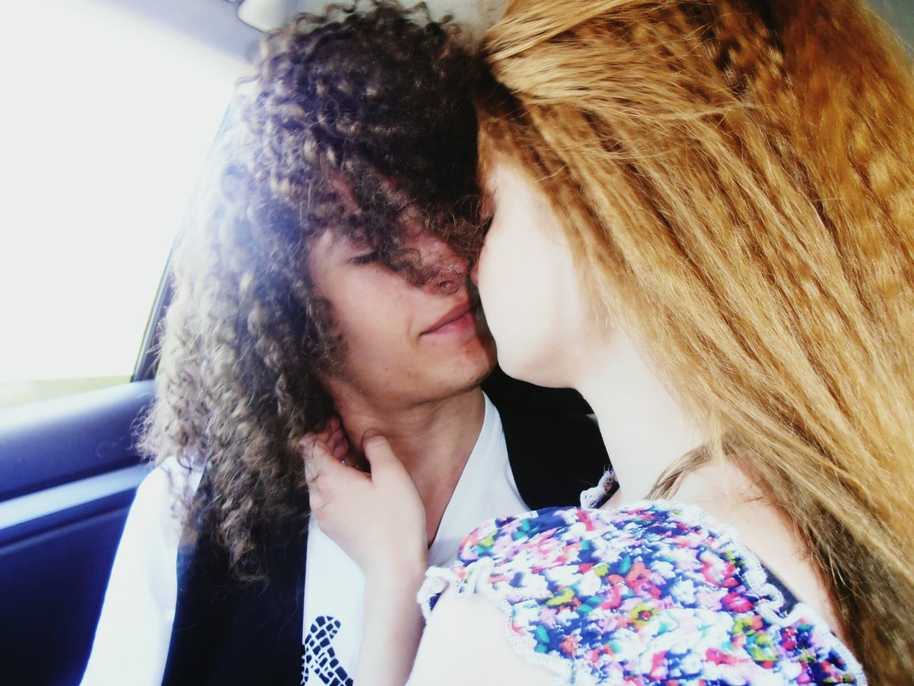 Couple kissing while traveling in car