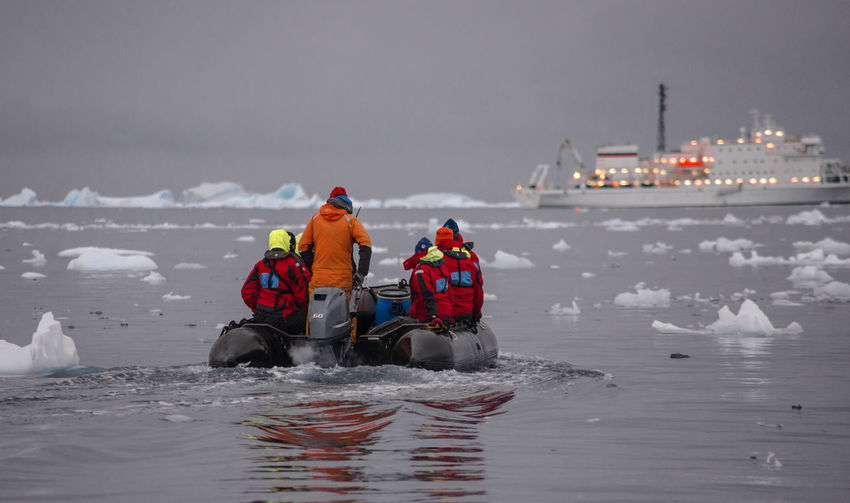 Rear View Of People On Inflatable Raft Amidst Icebergs In Sea During Winter