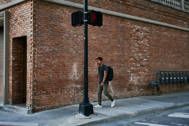 Man standing on street against wall
