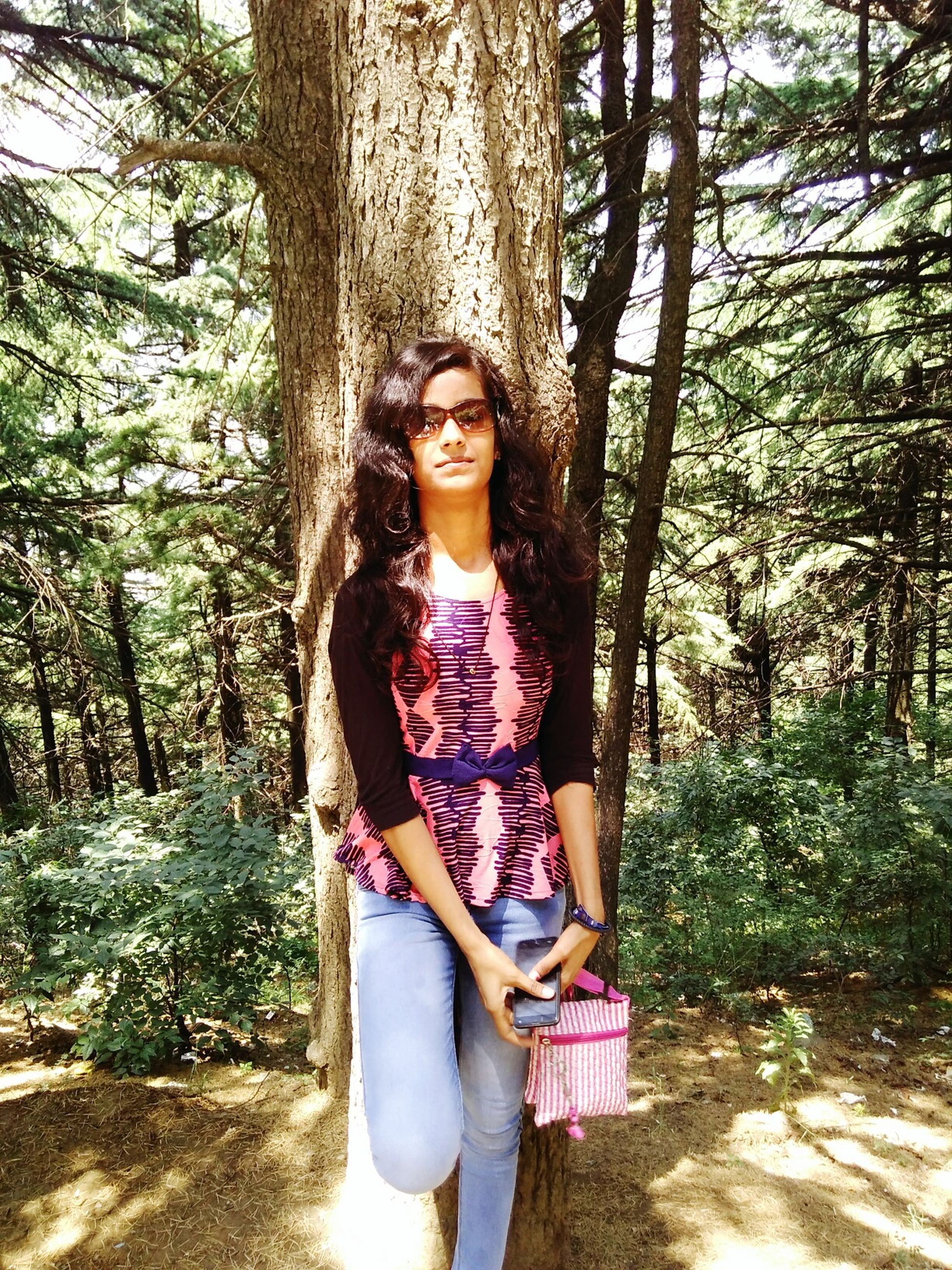 tree, tree trunk, lifestyles, forest, leisure activity, person, young adult, standing, young women, front view, full length, vacations, casual clothing, looking at camera, woodland, nature, day, non-urban scene, long hair, outdoors, tourism