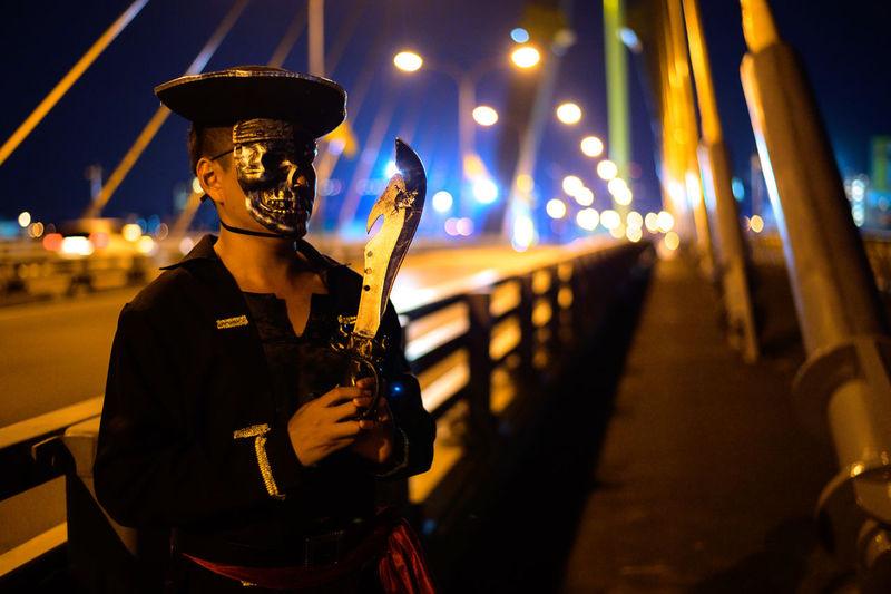 Man wearing mask holding knife on bridge at night