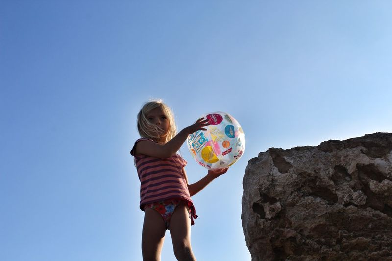 Girl With A Beach Ball Childhood Clear Sky Child Real People Outdoors Sky Cliff Ball Playing Beach Holiday Blue Sky