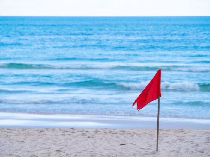 Red flag on beach against sky