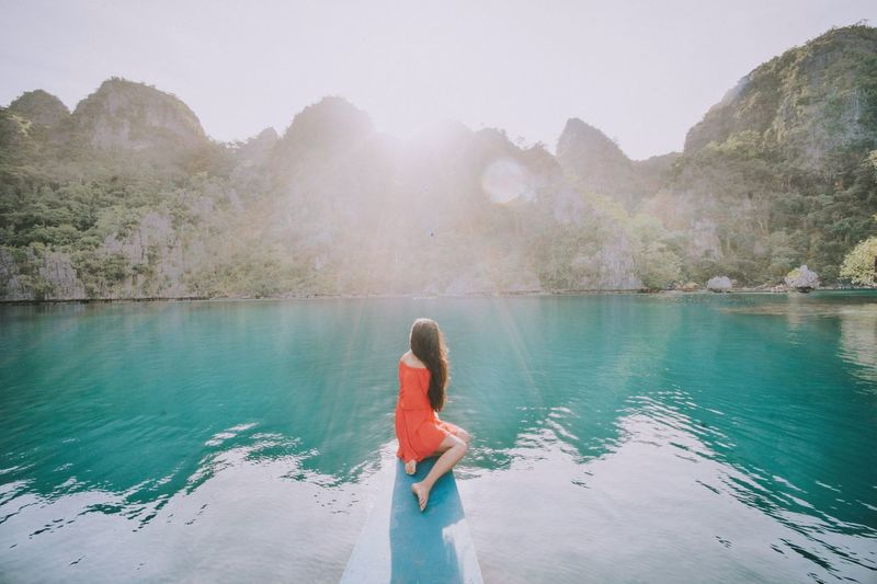 Side view of woman relaxing on jetty on sea by mountains against sky at coron island