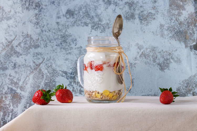 Healthy breakfast muesli, strawberries and yogurt with mango smoothie in glass mason jars. Served with fresh strawberry on white tablecloth with textured wall at background. Rustic style. Healthy Yogurt Food Background Fresh Breakfast Yoghurt Wooden White Muesli Berry Milk Granola Natural Health Sweet Fruit Organic Diet Meal Nutrition Flakes Freshness Delicious Cereal Jar Glass Mason Dairy Oat Table Dessert Grain Yougurt Oatmeal Vegetarian Morning Ripe Tablecloth Textured  Textile Rustic Spoon Snack Eating Kitchen Homemade Layered