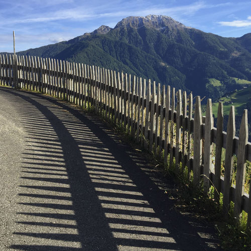 Shadow of fence on road against mountain range