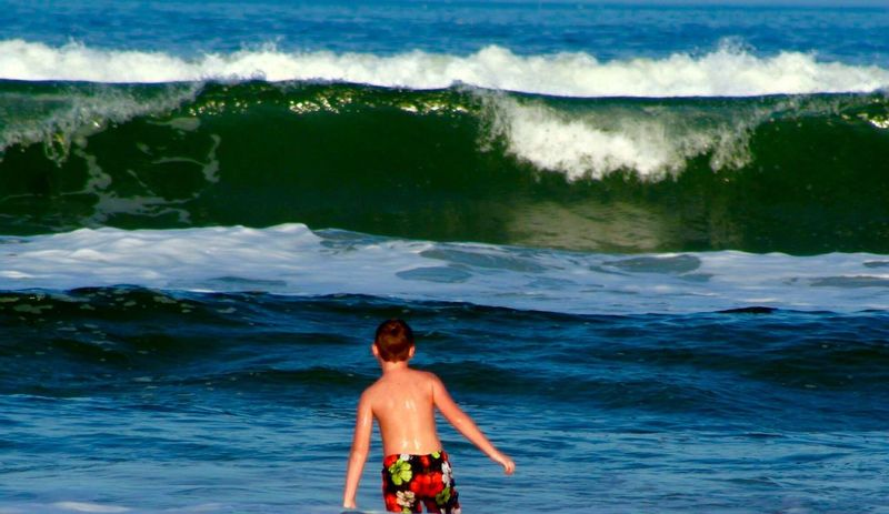 Little boy facing waves after a storm Stand Out From The Crowd Boy On Beach Looking At Big Surf Surf's Up