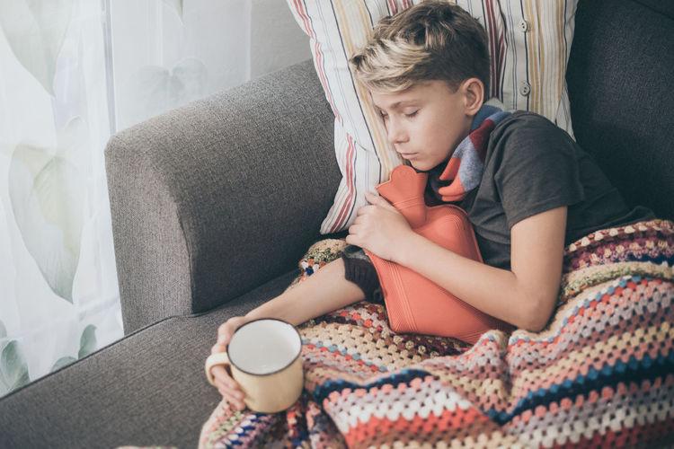 Ill boy sleeping with hot water bottle on sofa