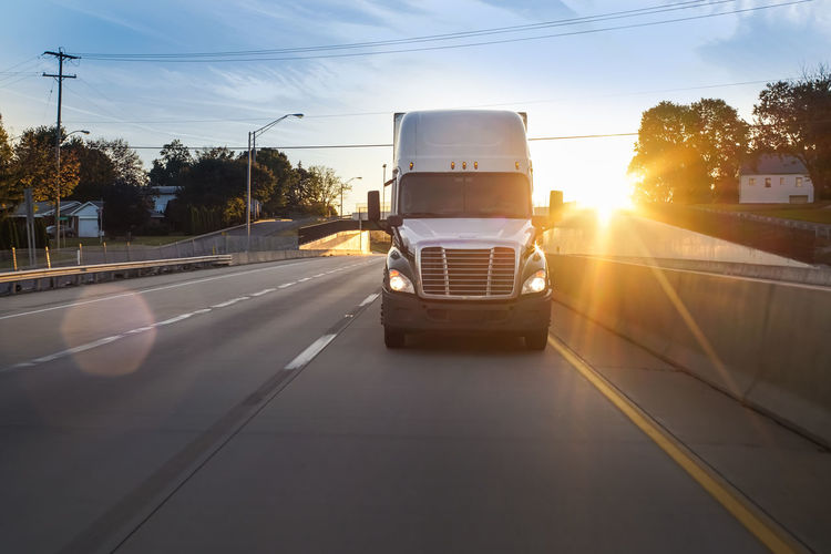 Freight truck rolling down the road at sunset Big Rig Logistics America Freight Transportation Highway Semi-truck Supply Chain Tractor Trailer Transportation Vehicle Truck Truckerslife