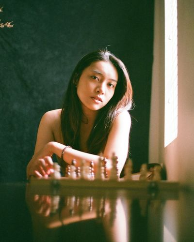 Portrait of young woman sitting by chess pieces on table