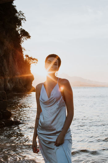 Young woman standing by sea against sky during brazilian sunset.