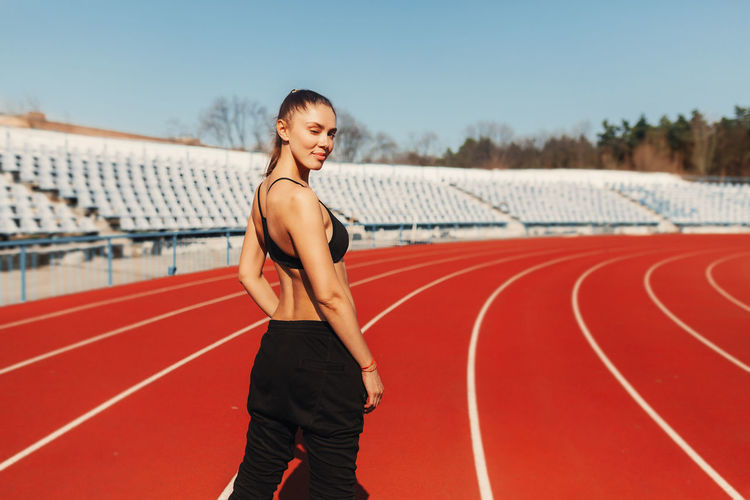 Portrait Of Female Athlete Standing On Running Track
