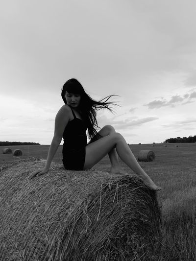 Full Length Of Young Woman Sitting On Hay Bale Against Sky