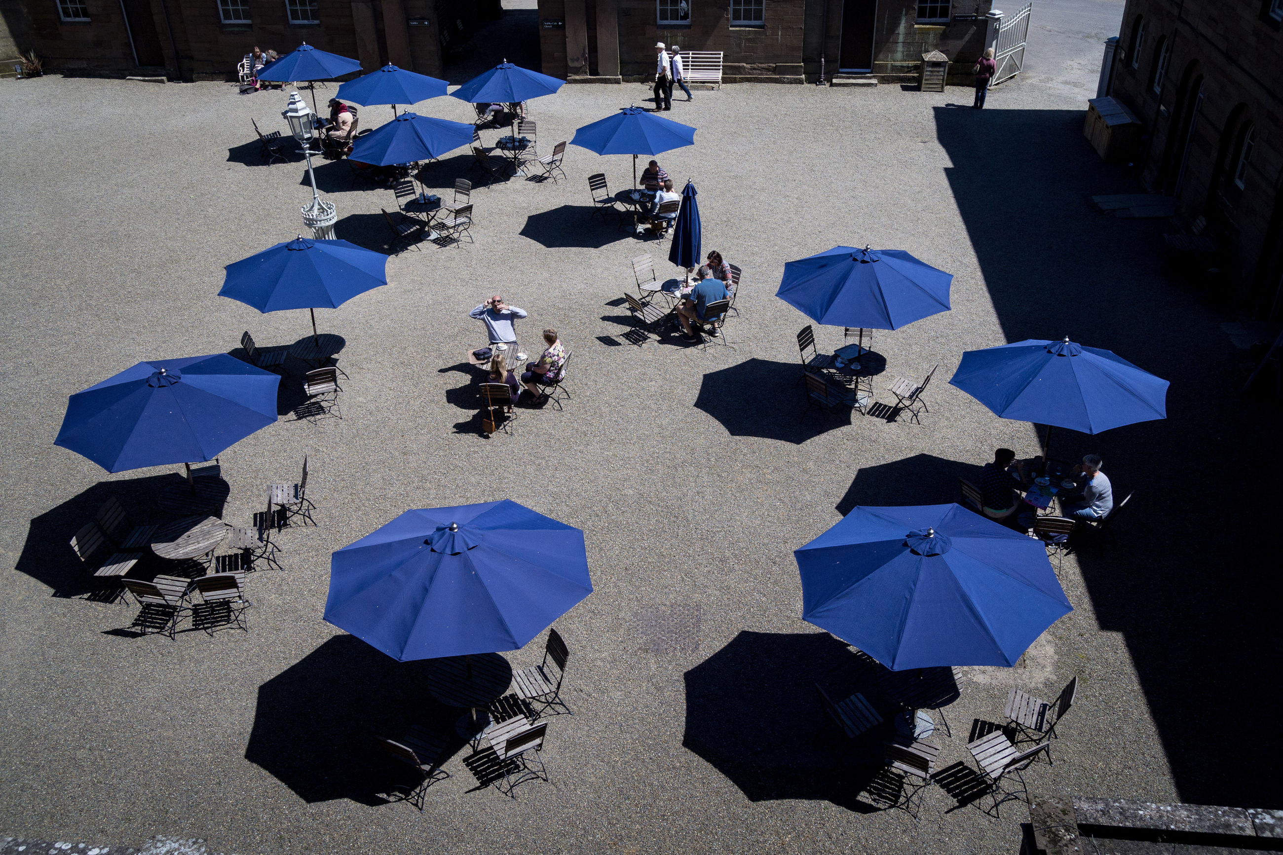 umbrella, protection, high angle view, group of people, parasol, security, crowd, real people, blue, city, nature, large group of people, sunlight, street, day, outdoors, shadow, chair, relaxation, rain