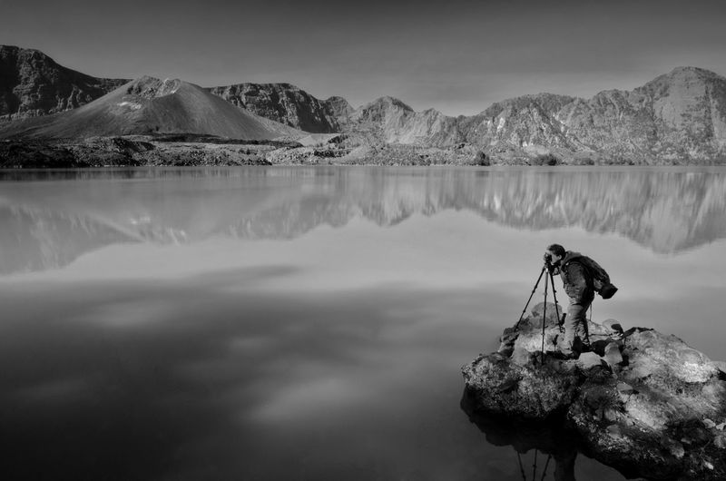 Beautiful nature background with unidentified hiker at Segara Anak Lake in early morning with blue sky. Mount Rinjani is an active volcano in Lombok, indonesia. Soft focus due to long exposure. Black And White Fine Art Lombok Indonesia Mount Rinjani Lombok Amazing View Black&white Fine Art Photography Black Amazing INDONESIA Wallpaper EyeEm Nature Lover EyeEm Backgrounds Sunrise Sunset Water Mountain Lake Snow Reflection Wilderness Area Sky Landscape Mountain Range Mountain Peak