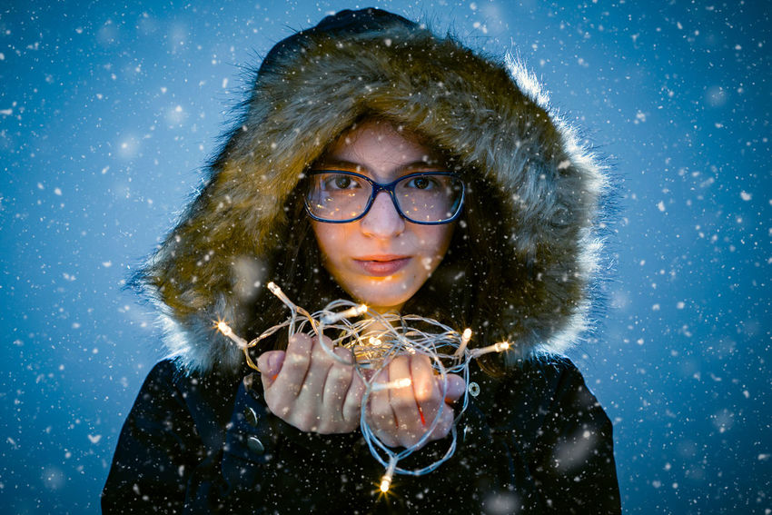 Snow wish Blue Blue Background Cold Temperature Eyeglasses  Headshot Looking At Camera One Person People Portrait Snow Snowflake Snowing Studio Shot Warm Clothing Winter