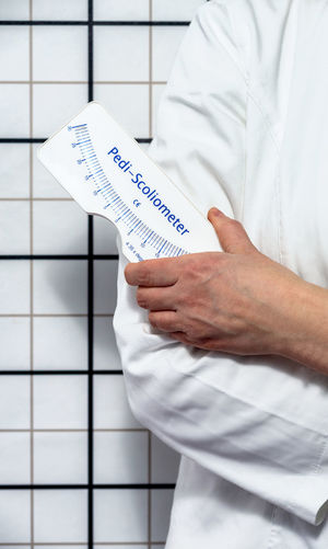 Midsection of man holding paper while standing against white wall