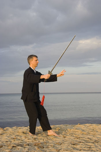 Full length of man practicing tai chi at beach against cloudy sky