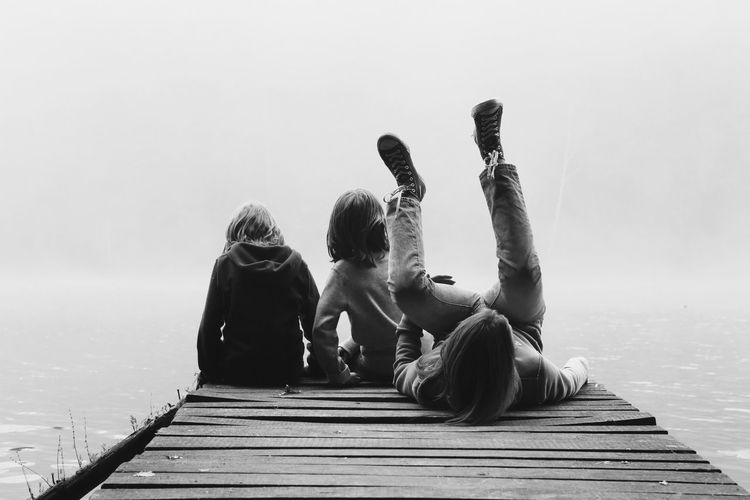 Rear View Of Friends With Arm Around Sitting On Pier By River During Foggy Weather