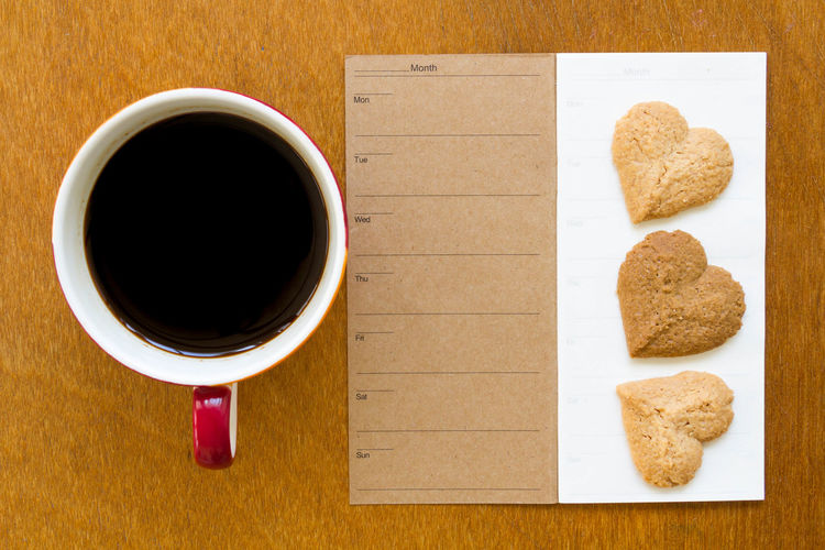 Directly Above Shot Of Black Coffee With Paper And Cookies On Table