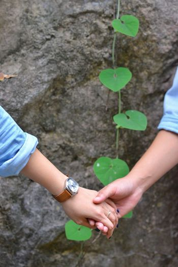 Midsection Of Couple Holding Hands Outdoors