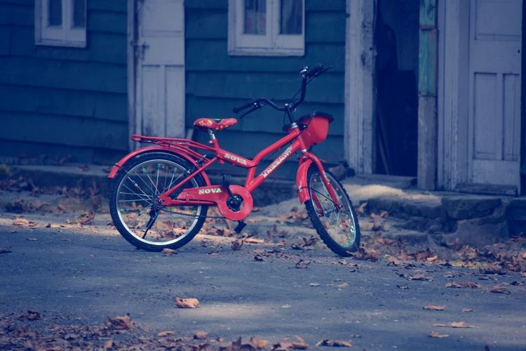 A bicycle Parked on a Road Bicycle Transportation Mode Of Transport Red Stationary No People Outdoors Day
