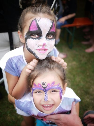 High angle portrait of sisters with face paint on field
