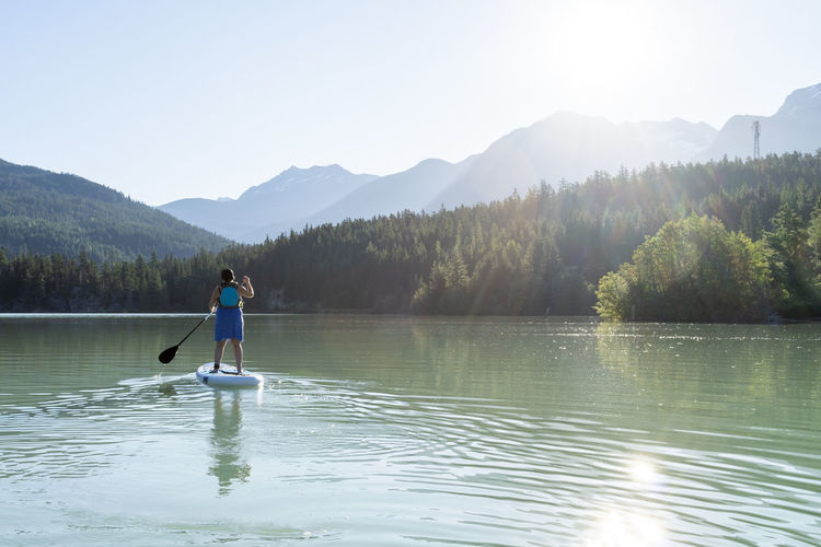 Man in lake against mountains