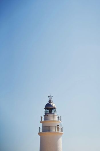 Low angle view of lighthouse by building against clear sky