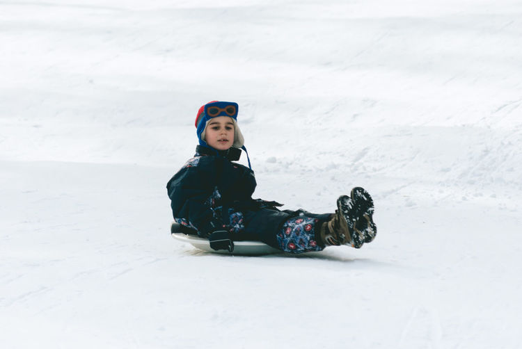 Childhood Cold Temperature Day Field Full Length Leisure Activity Lifestyles Nature One Person Outdoors People Real People Snow Snowboarding Warm Clothing Weather Winter