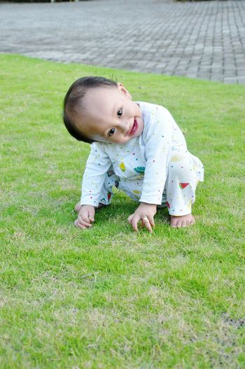 Cute baby boy with head cocked looking away while crouching on grassy field