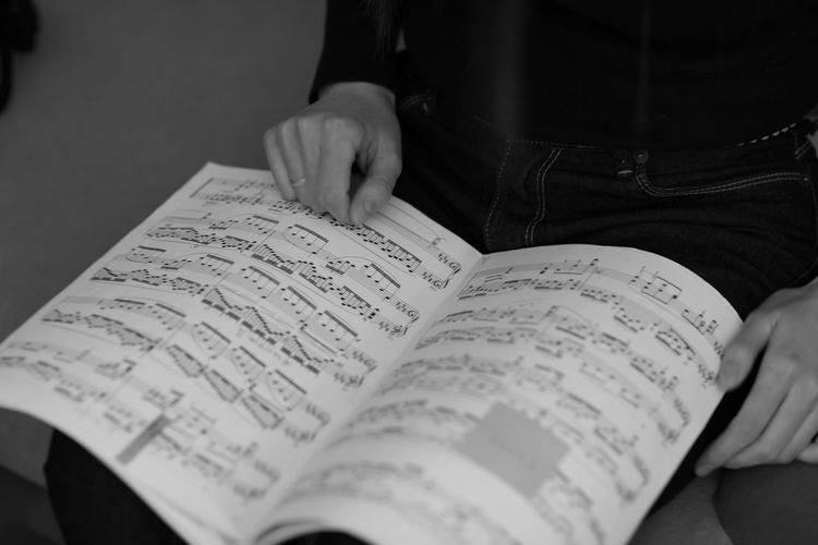 Midsection Of Person With Sheet Music